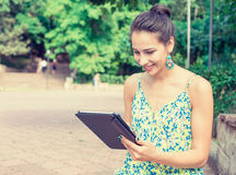 Den lyckliga kvinnan som använder den utomhus- minnestavladatoren i sommar, parkerar och att le Royaltyfri Bild