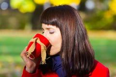 Den lyckliga kvinnan som dricker varmt te i höstligt, parkerar, hösten Royaltyfri Fotografi