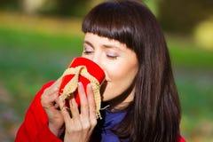 Den lyckliga kvinnan som dricker varmt te i höstligt, parkerar, hösten Arkivbild