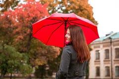 Den lyckliga kvinnan som går i höststad, parkerar Regnigt väder och gula träd omkring Royaltyfri Fotografi