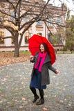 Den lyckliga kvinnan som går i höststad, parkerar Regnigt väder och gula träd omkring Arkivbild