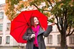 Den lyckliga kvinnan som går på höststad, parkerar Regnigt väder och gula träd omkring Royaltyfria Bilder