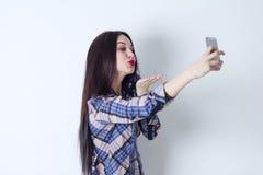 Den lyckliga kvinnan som gör selfie och, överför en kyss till kameran Fotografering för Bildbyråer