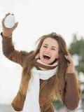 Den lyckliga kvinnan som kastar snow, klumpa ihop sig i vinter parkerar arkivbild
