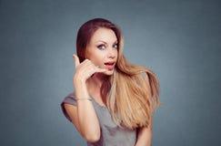 Den lyckliga kvinnan som ler visning, kallar mig för att underteckna gest med handen royaltyfri fotografi