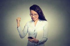Den lyckliga kvinnan som ser mobiltelefonen som ler pumpa näven, firar framgång Royaltyfria Bilder