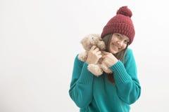 Den lyckliga kvinnan spelar med ett teddybear som isoleras på vit Arkivbild