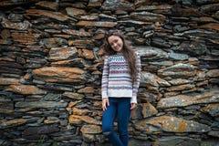 Den lyckliga kvinnan står på isolerad bakgrund av stenar royaltyfri bild