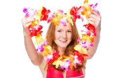 Den lyckliga kvinnan sträcker blom- lei för en ferie royaltyfria foton