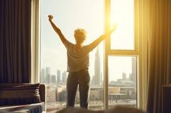 Den lyckliga kvinnan sträcker och öppnar gardiner på fönstret i morgon arkivfoto