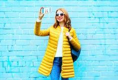Den lyckliga kvinnan tar en bild självståenden på smartphonen på tegelsten Arkivbilder