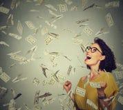 Den lyckliga kvinnan triumferar pumpa extatiska nävar firar framgång under ett pengarregn Royaltyfri Bild