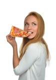 Den lyckliga kvinnan tycker om att äta skivan av peperonipizza med tomater Arkivbilder
