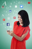 Den lyckliga kvinnan tycker om det sociala nätverket på mobiltelefonen Arkivbild
