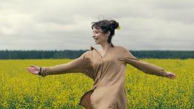 Den lyckliga kvinnan tycker om en sommar går i fält Blommor för sommarfältguling arkivbild