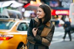 Den lyckliga kvinnan tycker om gå på vintertid på den New York City gatan och att göra att shoppa för jul arkivbilder