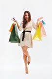Den lyckliga kvinnan visar påsar för en shopping På white Arkivfoton