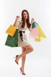 Den lyckliga kvinnan visar påsar för en shopping På white Fotografering för Bildbyråer
