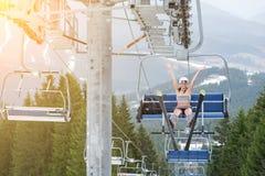 Den lyckliga kvinnliga sexiga skidåkaren sitter på skidlift, stigande hand upp och rider upp till överkanten av berget arkivfoton