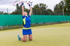 Den lyckliga kvinnliga spelareavverkningen på henne knä och lyftt henne händer är upp Fotografering för Bildbyråer