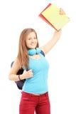 Den lyckliga kvinnliga studenten med påseinnehavet bokar och göra en gest happin Arkivbild