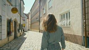 Den lyckliga kvinnliga turisten går, vänder omkring och ler i trevlig gata i Bratislava arkivfilmer