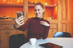 Den lyckliga kvinnlign fotograferar sig på celltelefonen under vilar i coffee shop Fotografering för Bildbyråer