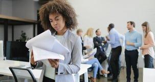 Den lyckliga le affärskvinnan som läser lyckade rapportdokument över möte av affärsfolk, team i modernt idérikt lager videofilmer