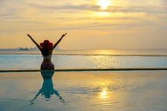 Den lyckliga le asia kvinnan med sugrörhatten kopplar av och lyx i simbassängen, bakgrundssolnedgång Royaltyfri Fotografi