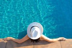 Den lyckliga le asiatiska kvinnan med sugrörhatten kopplar av och lyx i simbassäng på semesterorthotellet, livsstilen och den lyc
