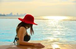 Den lyckliga le asiatiska kvinnan med sugrörhatten kopplar av och lyx i simbassängen, bakgrundssolnedgång Arkivbilder