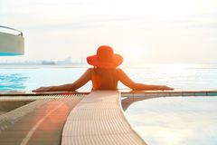 Den lyckliga le asiatiska kvinnan med sugrörhatten kopplar av och lyx i simbassängen, bakgrundssolnedgång Arkivbild
