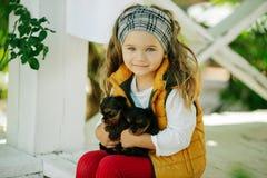 Den lyckliga le barnflickan bär varm kläder för mode med gulliga valpar av den yorkshire terriern utomhus arkivfoton