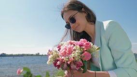 Den lyckliga le blomsterhandlareflickan i solglasögon samlar buketten av härliga blommor på äng nära floden lager videofilmer