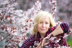 Den lyckliga le Caucasian blonda kvinnan med långa hårleenden och det lyckliga near blomstra körsbärsröda trädet för plommon, tyc Royaltyfria Bilder
