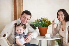 Den lyckliga le familjen med en som är årig, behandla som ett barn flickan inomhus arkivbilder