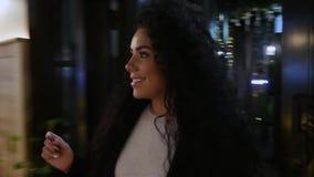 Den lyckliga le flickan med lockigt hår kommer i en restaurang lager videofilmer