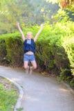 Den lyckliga le flickan som hoppar på, parkerar i dagtiden arkivbilder