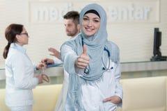 Den lyckliga le gladlynta kvinnliga muslimdoktorn med tummar gör en gest upp Royaltyfri Foto