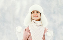 Den lyckliga le kvinnan som bär en tröja, och hatten över vinter parkerar Arkivbild