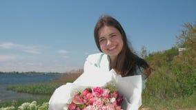 Den lyckliga le kvinnan visar den härliga blommande buketten av blommor på äng nära floden arkivfilmer