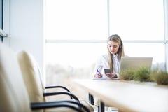 Den lyckliga le kvinnliga operatören för telefonen för kundservice på arbetsplatsen gör meddelandet i anteckningsbok Arkivbilder