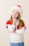 Den lyckliga le lilla flickan i julhatt drömmer Royaltyfri Bild