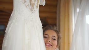 Den lyckliga le nätta bruden är tycka om och krama hennes stilfulla bröllopsklänning arkivfilmer