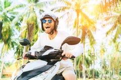 Den lyckliga le och skrikiga manliga turisten i hj?lm och solglas?gon som rider mopedsparkcykeln under hans tropiska semester g?m fotografering för bildbyråer