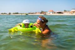Den lyckliga le pojken simmar i en rubber diskett med en ung moder av Arkivfoton