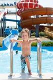 Den lyckliga le pysen i kortslutningar som står den near simbassängen i vatten, parkerar med vattenrörglidbanor Arkivfoto