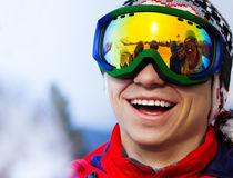 Den lyckliga le snowboarderen skidar in maskeringsståenden arkivbild