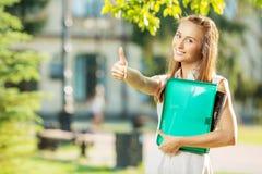Den lyckliga le studentkvinnan står i universitetsområdet royaltyfri fotografi