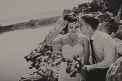 Den lyckliga le unga bruden och brudgummen och att gå på stranden och att kyssa som kramar bröllopceremoni nära, vaggar, havet royaltyfria foton